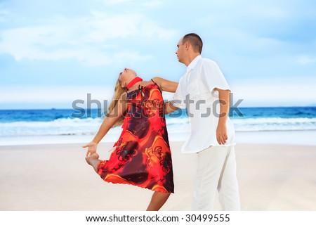 Young couple dancing near the ocean