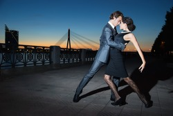 young couple dancing tango on the quay of the river at night