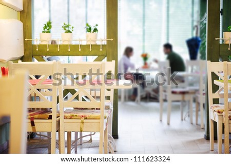 Young couple dating in stylish cafe. Primary focus on empty chairs.