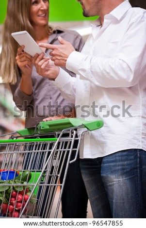 Young couple deciding with spiral notebook while shopping at supermarket - stock photo