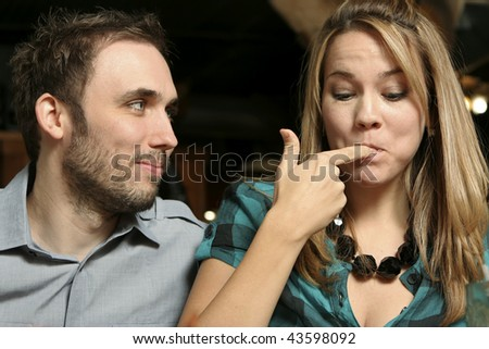 young couple dining at a  restaurant. Woman licking fingers. Shallow dof with background blurred