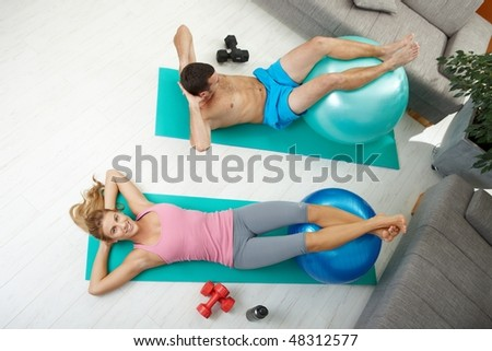 Young couple doing abdominal crunch using fit ball at home, overhead shot.