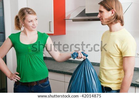 Young couple doing chores and cleaning the apartment, he is not too happy to have to get out the garbage weaseling out of the task