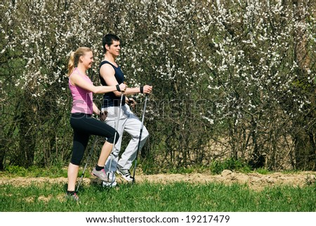 Young couple doing Nordic walking in spring