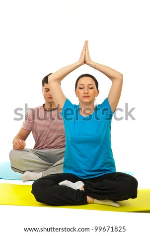 Young couple doing yoga and sitting on gymnastics mats against white background