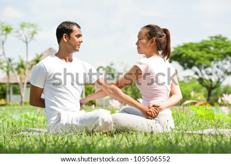 Young couple doing yoga exercise in the park
