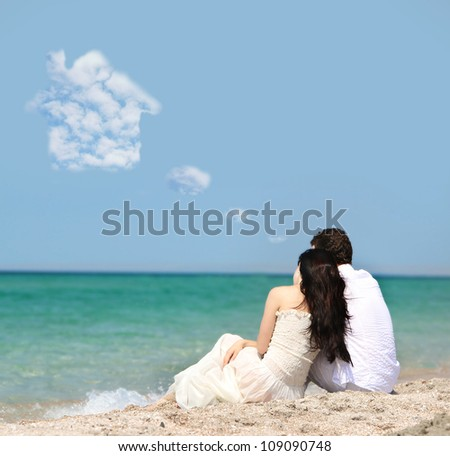 young couple dreaming about house on beach