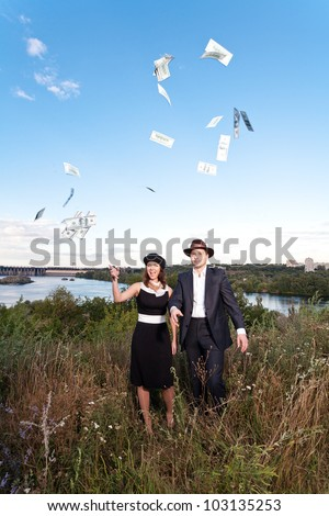 Young couple dressed as 30-s mobsters tossing money into the air