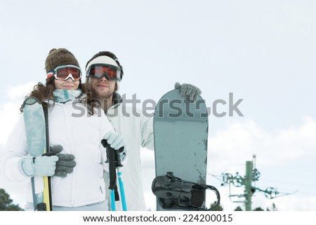 Young couple dressed in ski wear, man holding snowboard, woman holding ski sticks