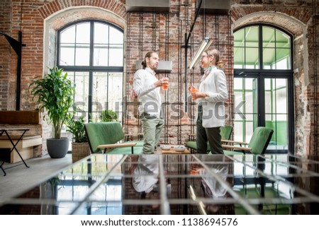 Young couple dressed in white standing together with drinks during the conversation in the beautiful spacious loft interior #1138694576