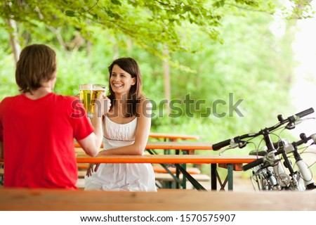 Young couple drinking beers at picnic table on bike outing