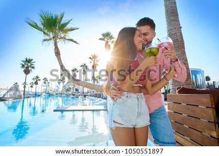 Young couple drinking cocktail in a resort pool in summer vacation #1050551897