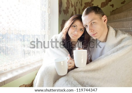 young couple drinking coffee in the morning and laughs at his home