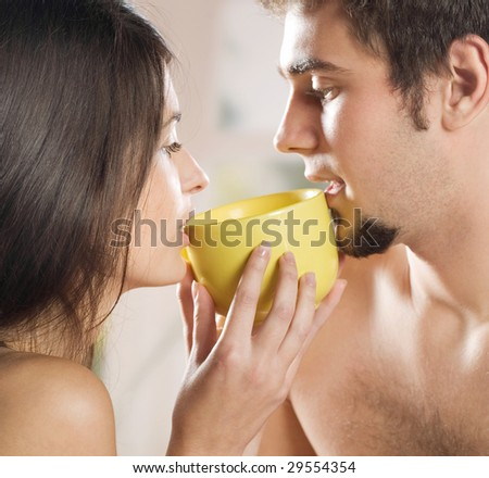 Young couple drinking on the bed in bedroom