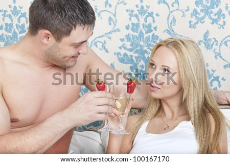 Young couple drinking sparkling wine in bed