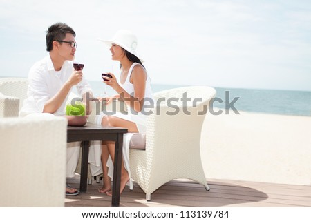 Young couple drinking wine by the sea