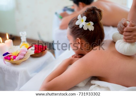 young couple during massage with spa herbal compress , relaxing couple concept