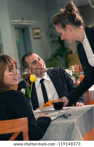 Young couple eating dinner with a waitress serving food at a restaurant.