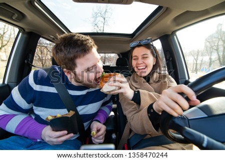 young couple eating fast food in car. modern rhythm lifestyle #1358470244