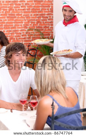 Young couple eating out in a pizzeria - stock photo