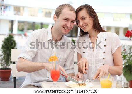 Young couple eating pizza in cafe