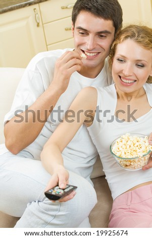 Young couple eating popcorn and watching TV together at home