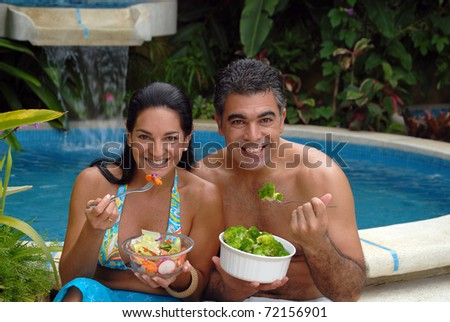 Young couple eating salad behind a swimming pool.