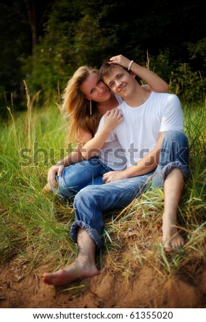 young couple embrace in high grass