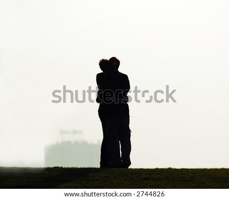 Young couple embracing and kissing at sunset