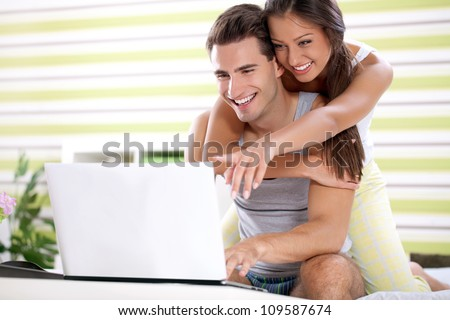 Young couple embracing and  together looking laptop, bedtime
