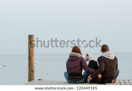 Young couple embracing dog looking at the sea