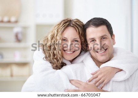 Young couple embracing in robes at home