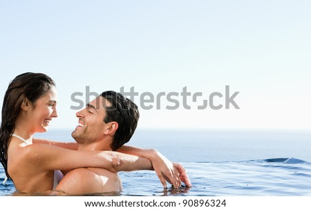 Young couple embracing in the pool