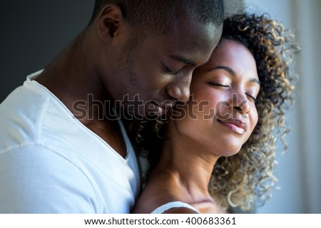 Young couple embracing together at home