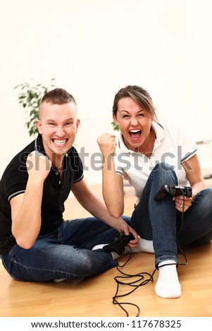 Young couple emotionally with passion play video games at home on the floor