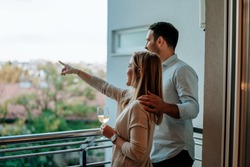 Young couple enjoy drinking wine at balcony. Woman pointing at something.