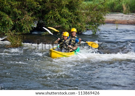 Young couple enjoy white water kayaking in Mae Rawa  river , North of Thailand