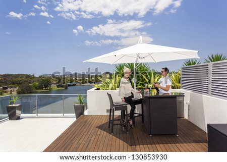 Young couple enjoying a drink on modern balcony
