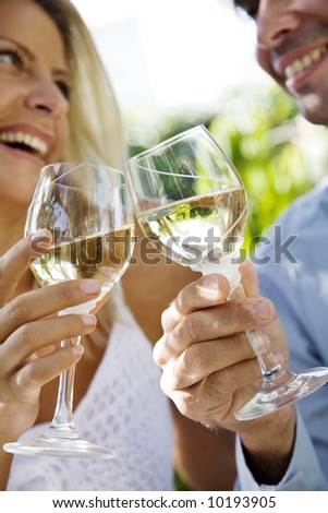 young couple enjoying a glass of white wine in the garden