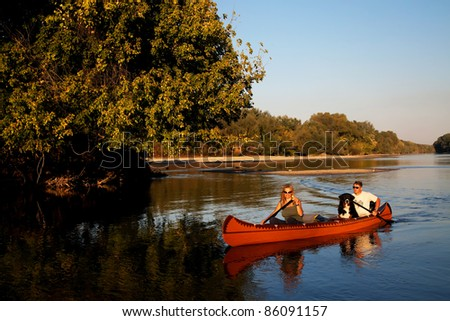 Young couple enjoying a trip in a canoe - sunset light
