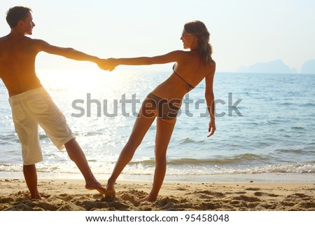 Young couple enjoying each other on a tropical beach at sunset