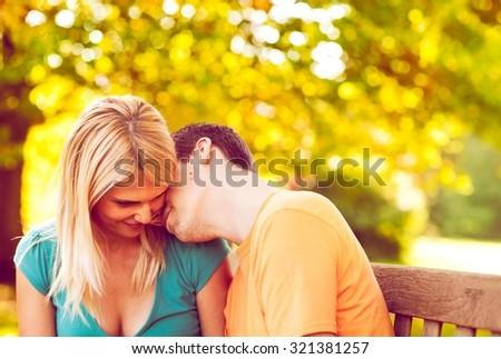 Young couple enjoying in the park on a sunny late summer day.