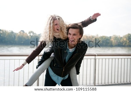 Young couple enjoying life together outdoor - man holding woman who pretends to fly