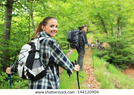 Young couple enjoying nordic walking in a forest