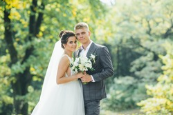 Young couple enjoying romantic moments while walking in the park. Stylish bride and groom posing and kissing in the park on their wedding day. Elegant bride in beautiful white dress, groom in a suit.