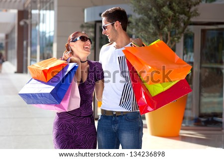 Young couple enjoying shopping. Happy young couple embracing each other, having fun during shopping, carrying colorful shopping bags