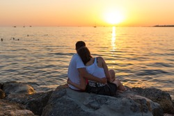 Young couple enjoying the sunset on the beach.