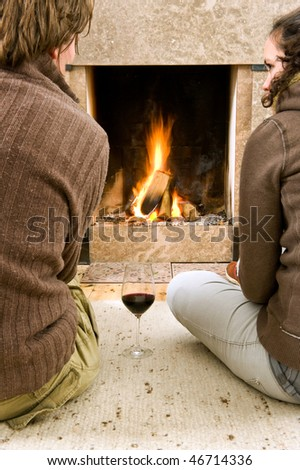 Young couple enjoying the warmth of a fire with a glass of wine