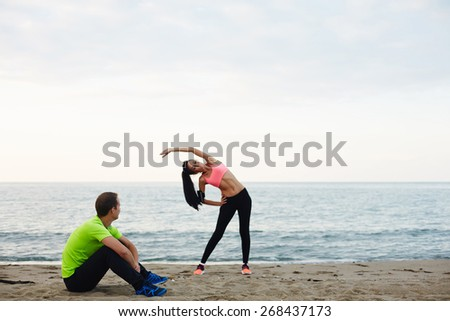 Young couple exercising and enjoying time outdoors, young fitness woman doing physical stretch exercise while her boyfriend taking break, couple working out on the beach at evening time