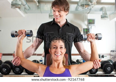 Young couple exercising in gym with weights, one of them is personal trainer